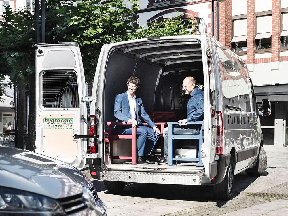 2 Mitarbeiter sitzen hinten auf der Ladefläche im Van